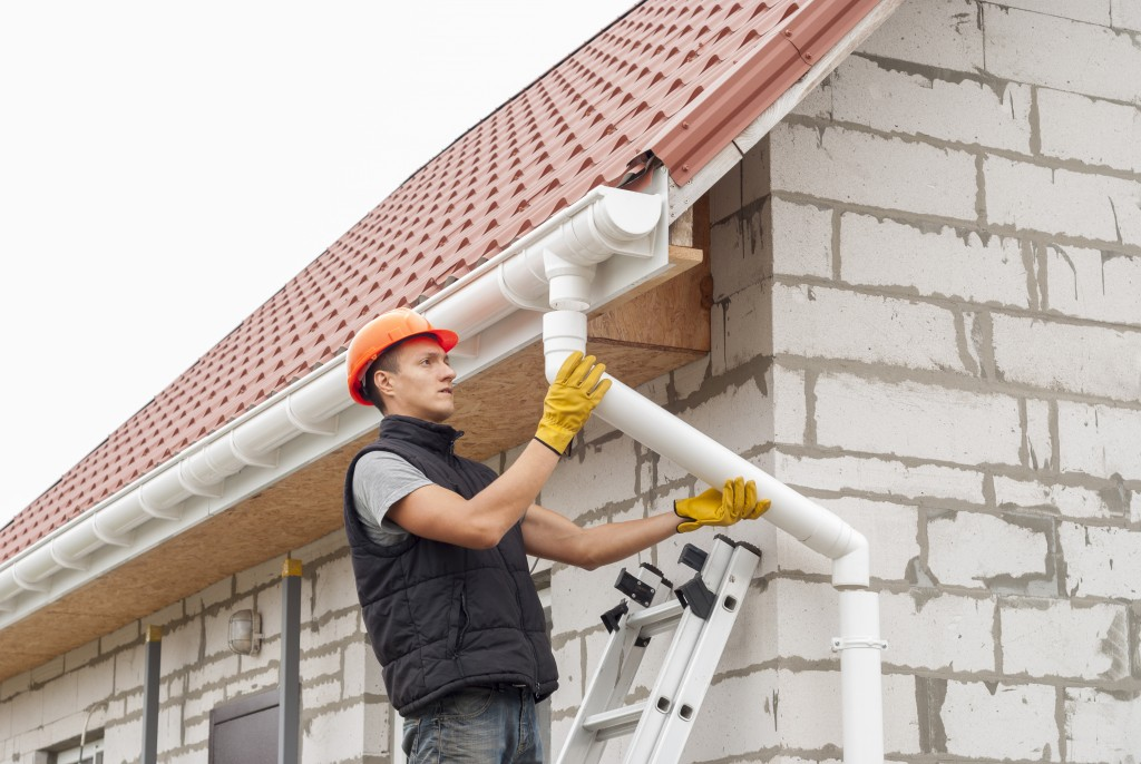 man fixing the roof downspout