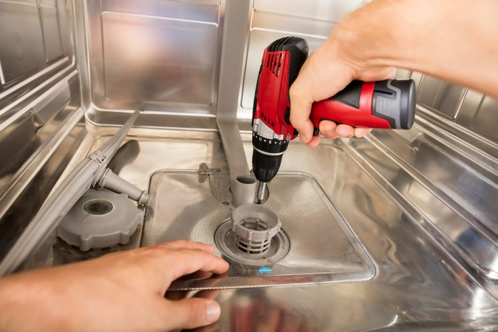 man using an electronic screwdriver to fix the dishwasher