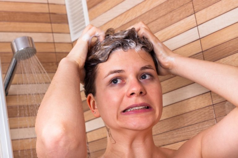 woman showering experiencing water heater problems