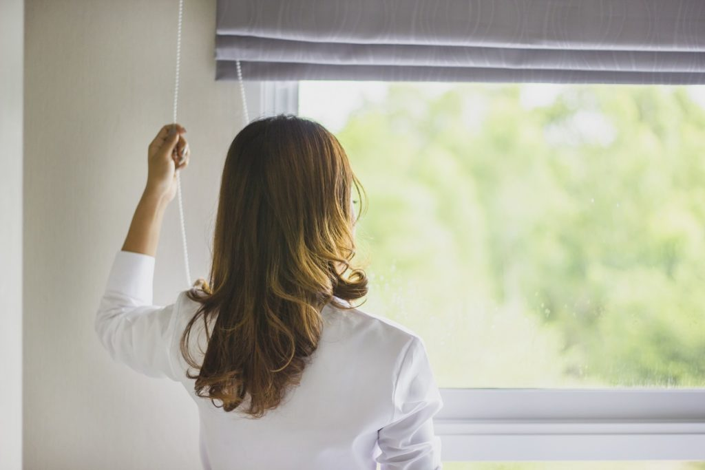 woman closing the blinds