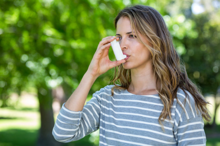 Adult female using inhaler