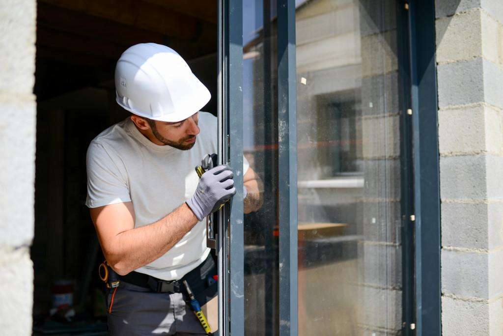 man fixing screen door