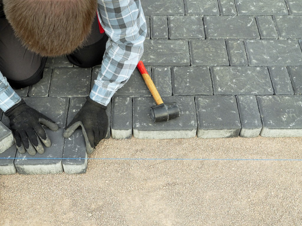 man placing stone flooring