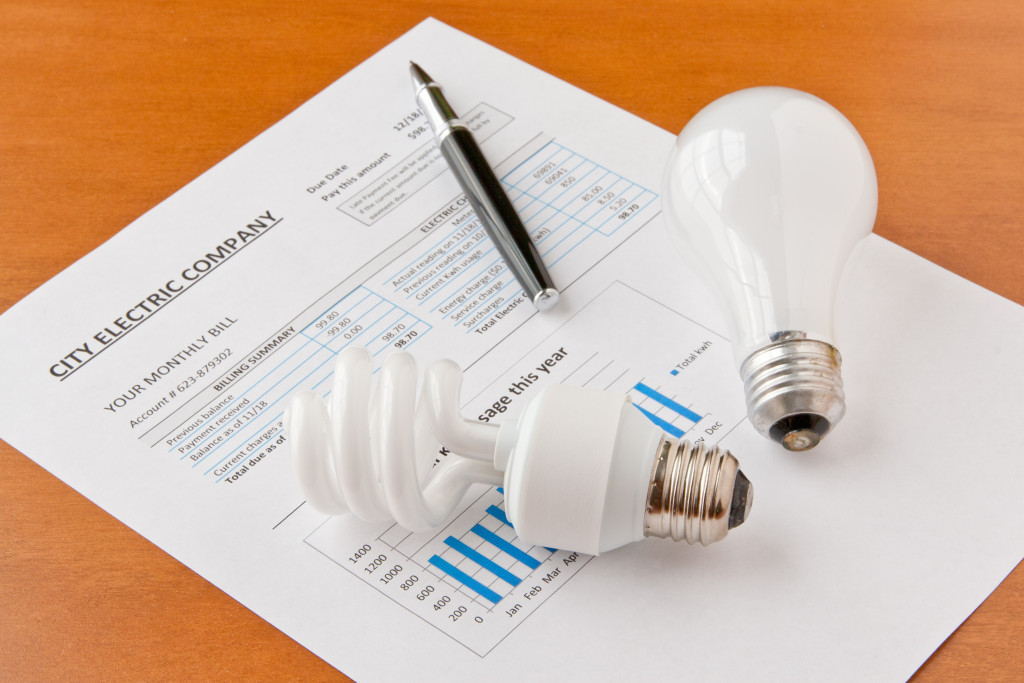 Energy efficient and incandescent bulbs on electric bill. Energy efficient house concept. selective focus