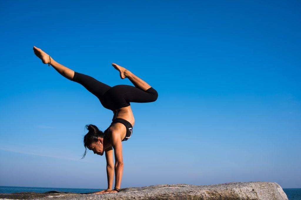 woman doing acrobatics a top a mountain