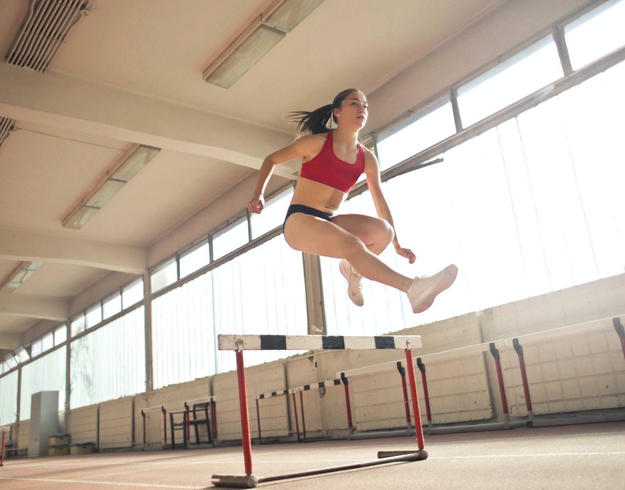 woman jumping over an obstacle
