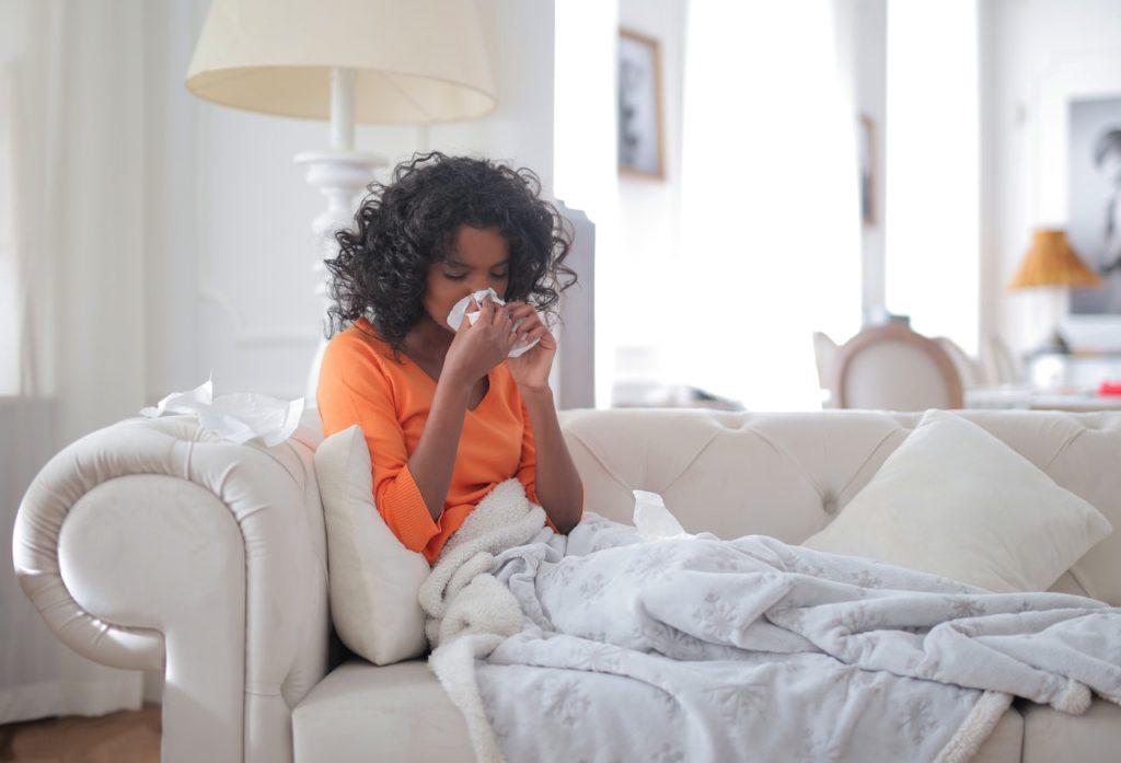 girl sneezing holding tissue