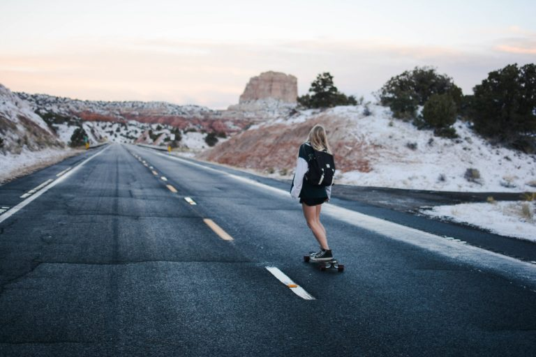 woman skateboarding on the road