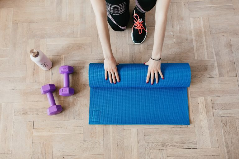 woman unfolding a yoga mat