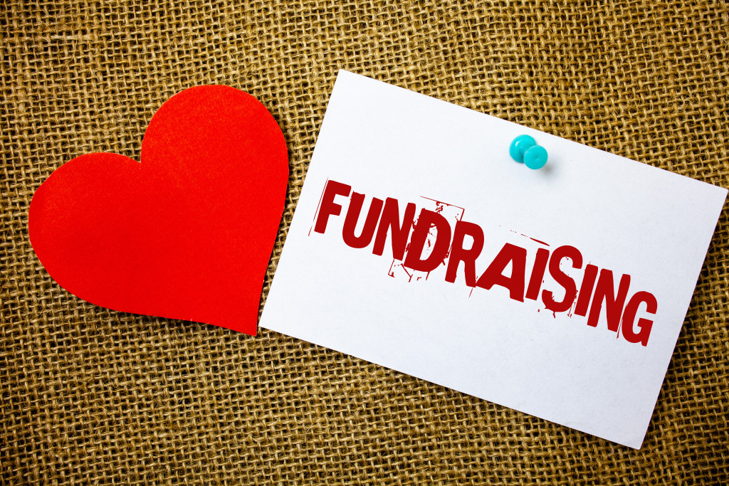 """a heart and a paper with the word """"fundraising"""" printed on it"""