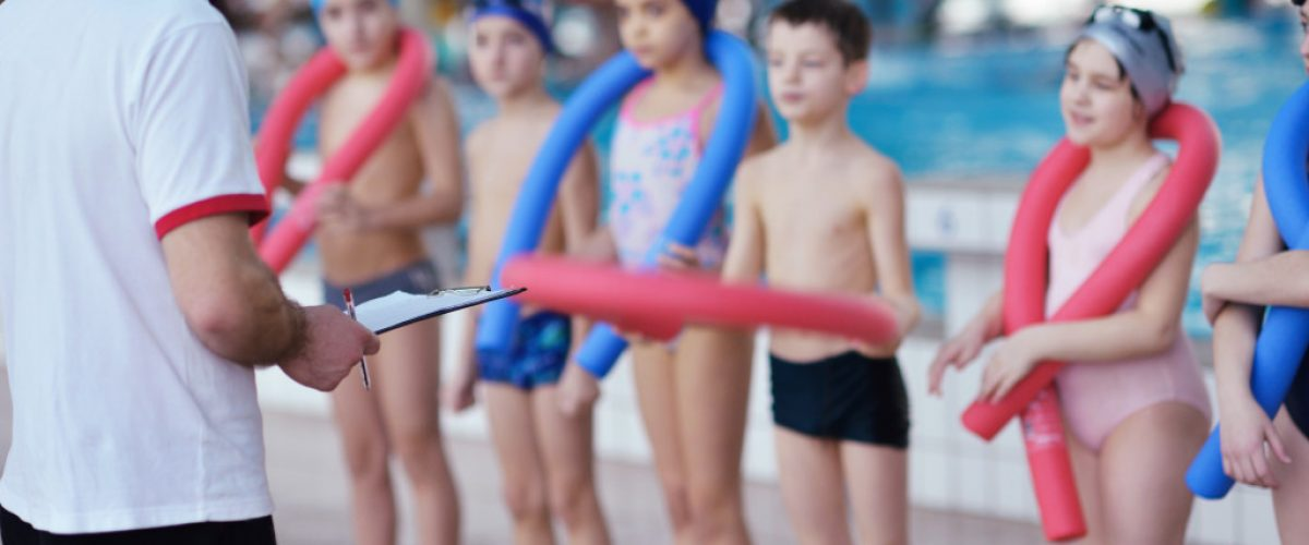 Kids group at swimming pool class learning to swim