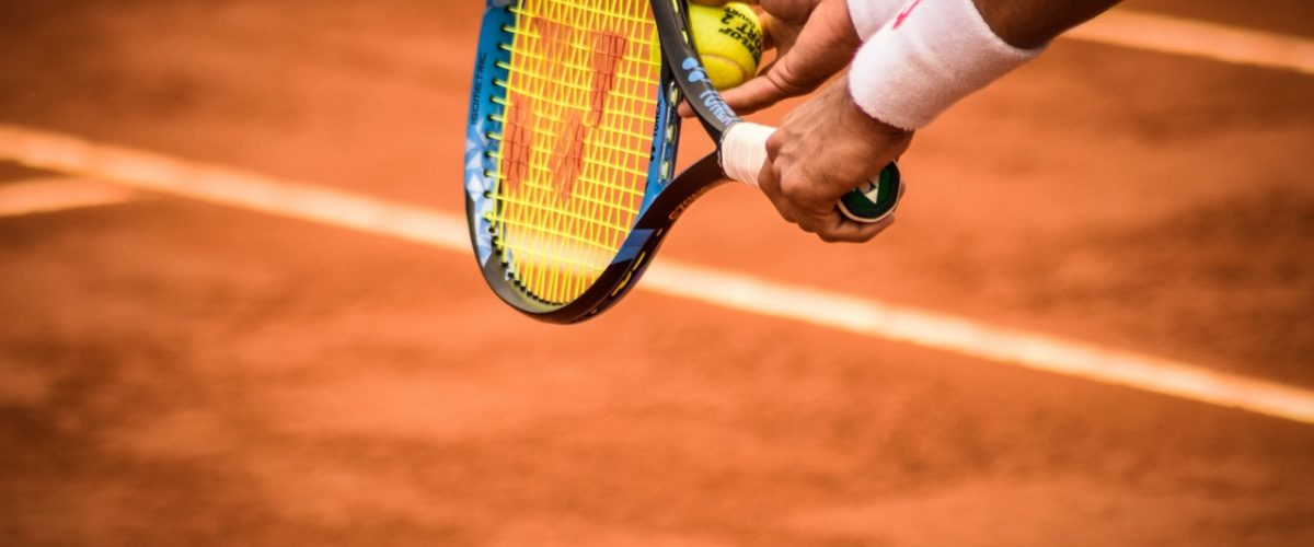 holding tennis racket and ball