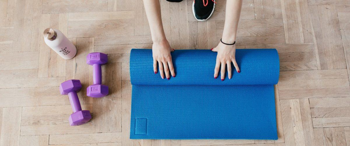 woman unfolding a yoga mat