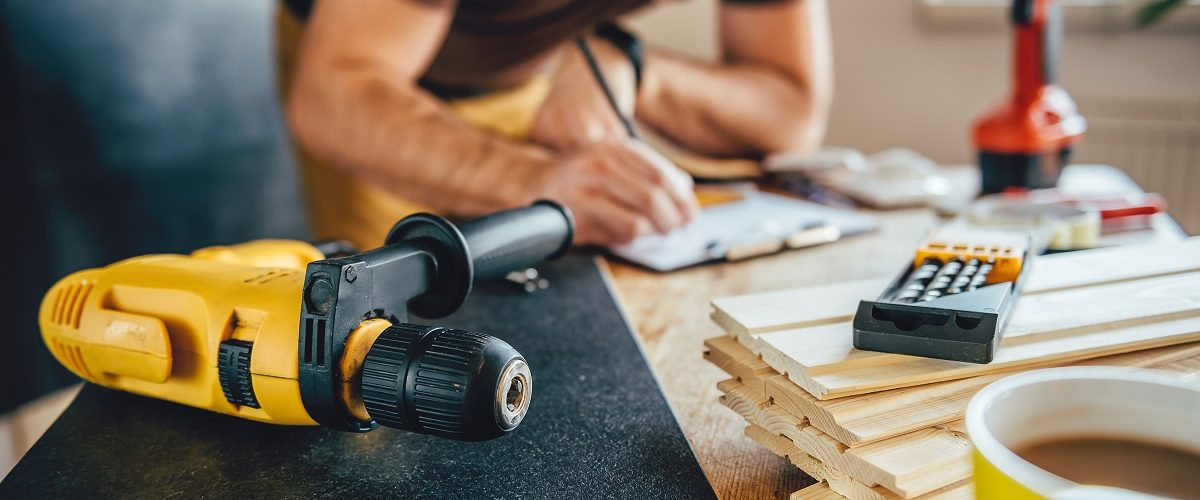 Man measuring a piece of wood before drilling it